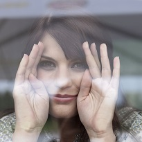 Germany, Cologne, Young woman looking through window, smiling, portrait